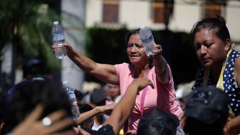 Una mujer reparte agua a los integrantes de la caravana en México