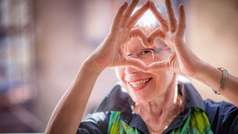 Mujer mayor haciendo un corazón