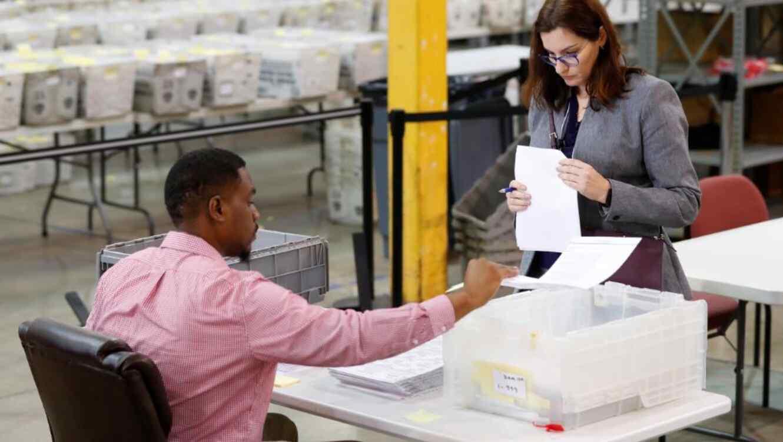 Un observador de un partido republicano, a la derecha, observa que un empleado de la oficina del Supervisor de Elecciones del Condado de Palm Beach este jueves 15 de noviembre de 2018, en West Palm Beach, Florida.