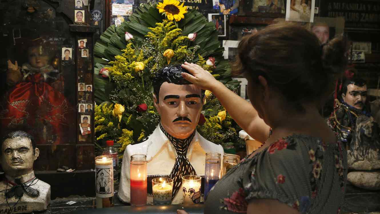 Una mujer toca una estatua de Jesús Malverde