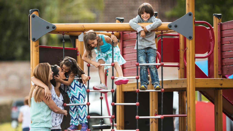 Madres y hijos en patio de juegos