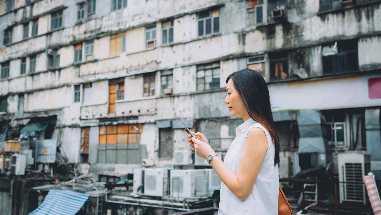 Mujer con iPhone en barrio pobre