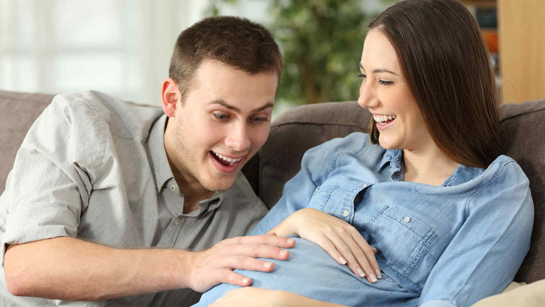 Padre tocando la panza de su esposa embarazada