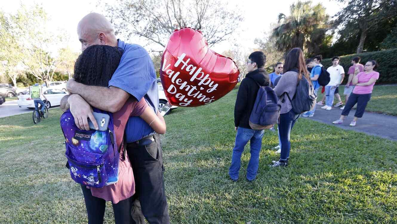 Familiares se abrazan después de un tiroteo en la escuela secundaria Marjory Stoneman Douglas el 14 de febrero de 2018, en Parkland, Florida.