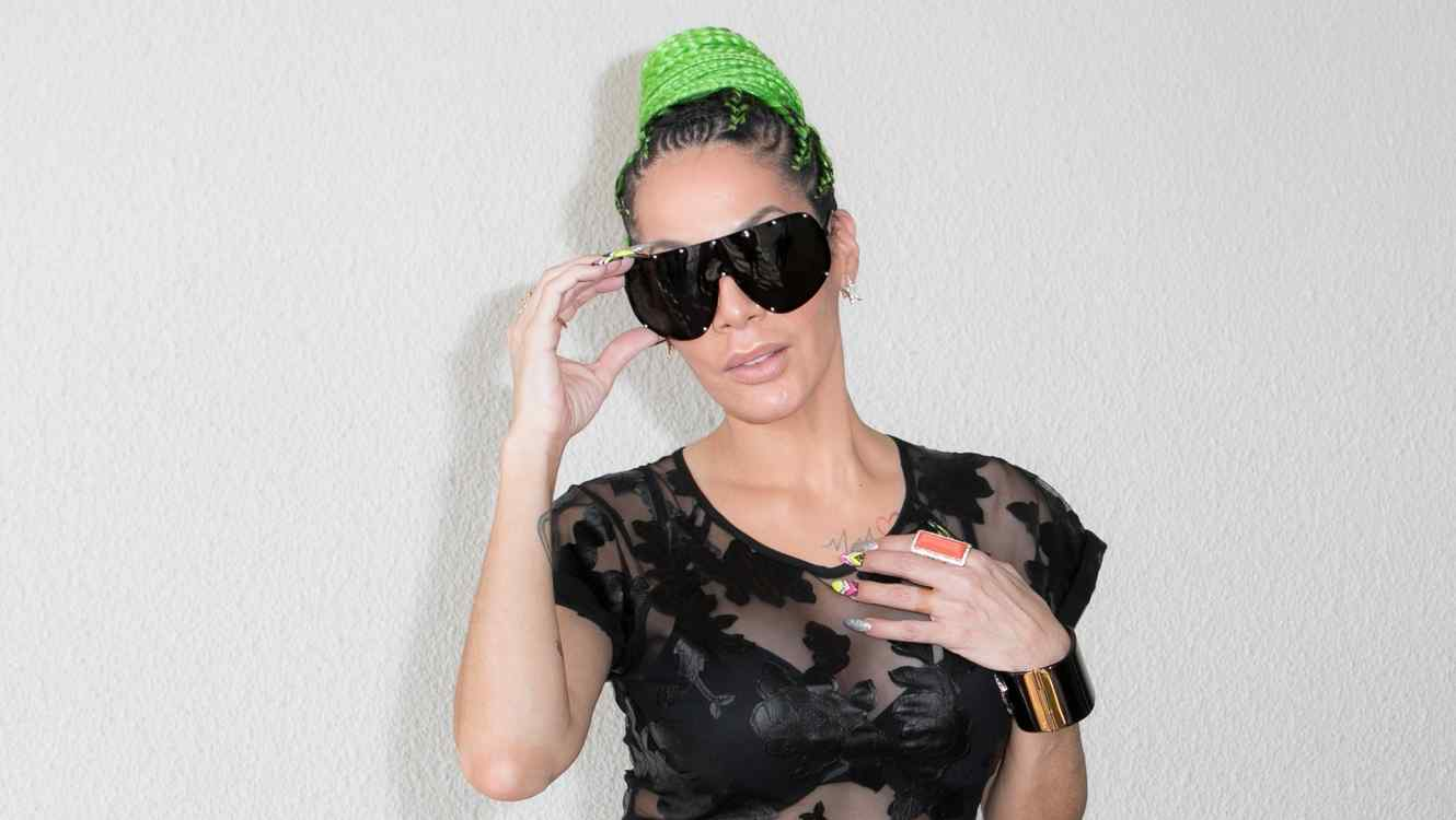 Ivy Queen poses with glasses and green hair