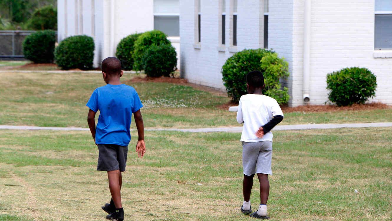 Niños caminan cerca de viviendas para personas de bajos ingresos en Charleston, Carolina del Norte