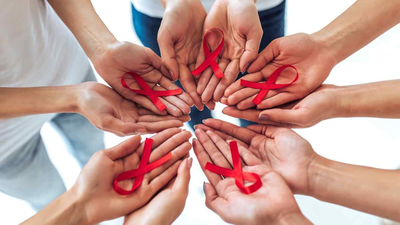 Personas sosteniendo cintas rojas