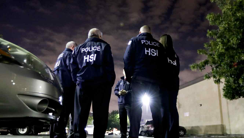 Agentes del Servicio de Inmigración y Aduanas se reúnen antes de una auditoría a una tienda de autoservicio en esta fotografía de archivo