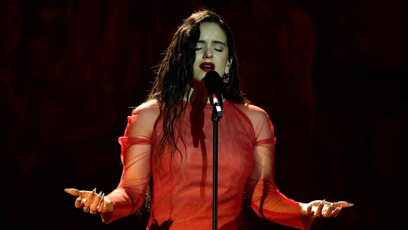 Rosalia sings while wearing a red dress.