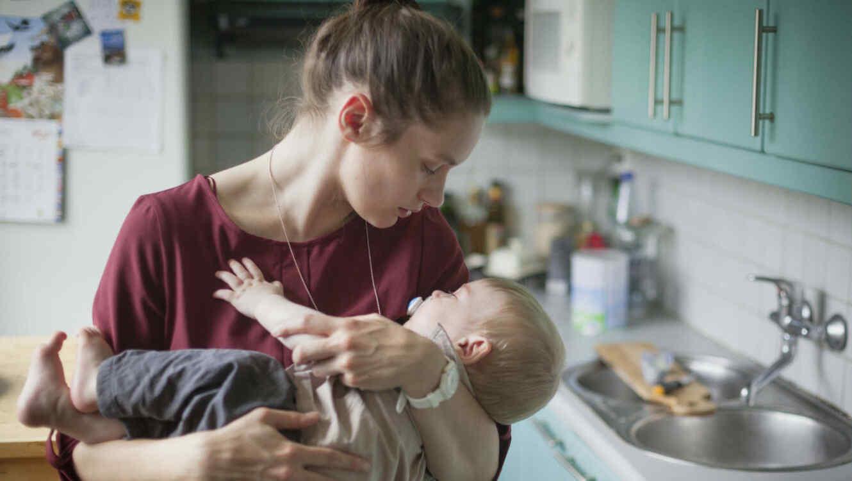 Mamá cargando a su bebé dormido