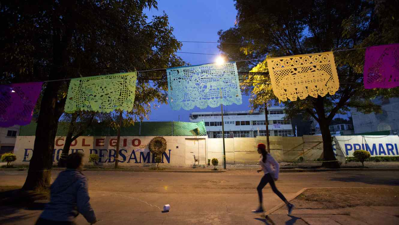 En esta fotografía de archivo se ve a una niña jugando a la pelota en el patio de una escuela primaria en México adornada para el Día de Muertos