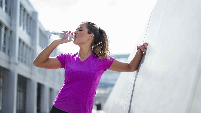 Mujer tomando agua embotellada