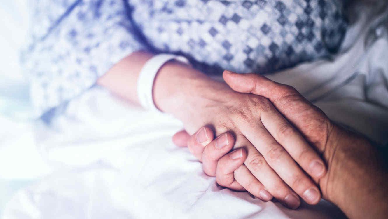 Paciente en hospital da la mano