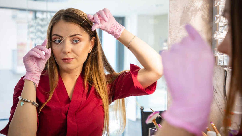 Mujer depilando sus cejas