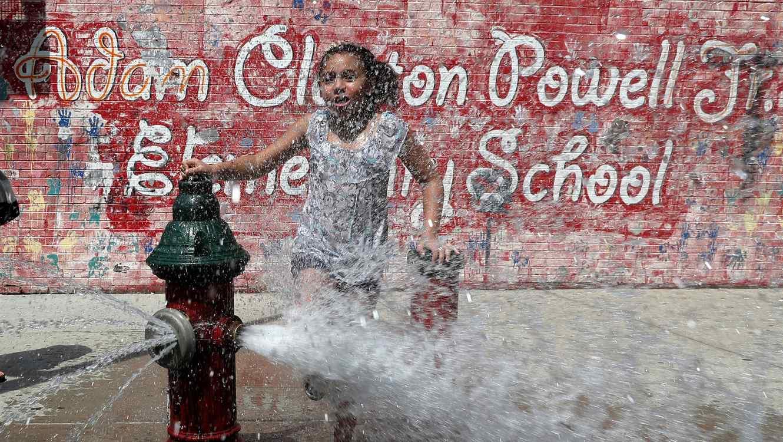Una niña se refresca en Manhattan en julio de 2019/Reuters