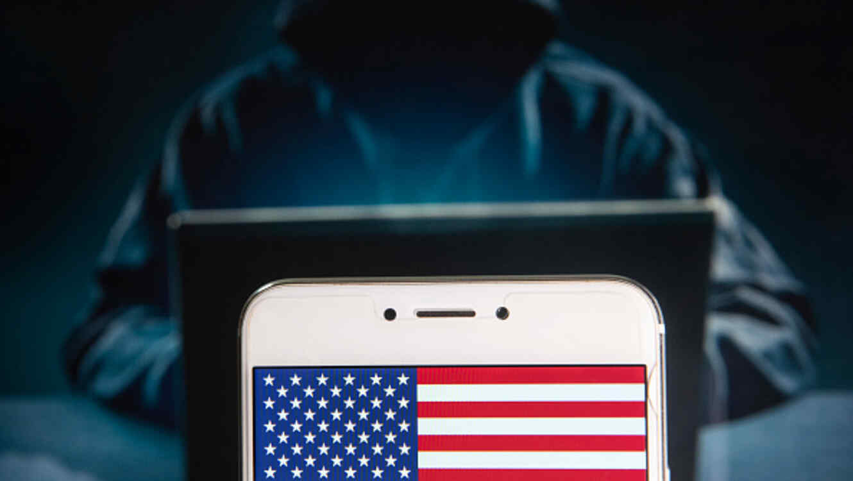 En esta ilustración aparece un teléfono móvil con la bandera estadounidense y en el fondo la figura de un pirata cibernético.