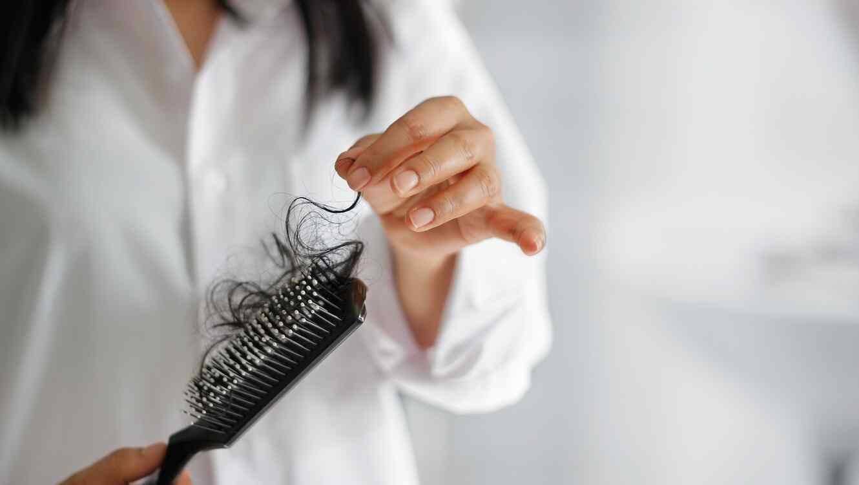 Mujer limpiando cepillo con mucho cabello