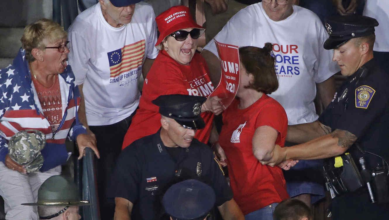 La policía acompaña a una manifestante fuera del recinto en el que se celebraba un acto de Trump este jueves en Manchester (New Hampshire).