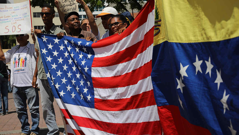 Oponentes de Nicolás Maduro sostienen las banderas de Estados Unidos y Venezuela.