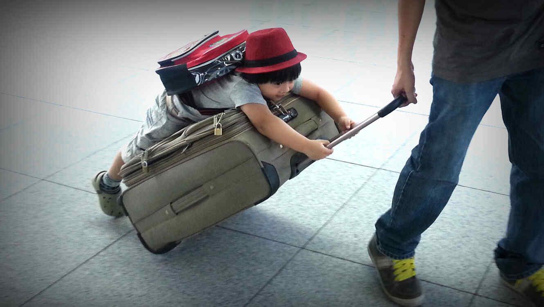 Niño encima de maleta