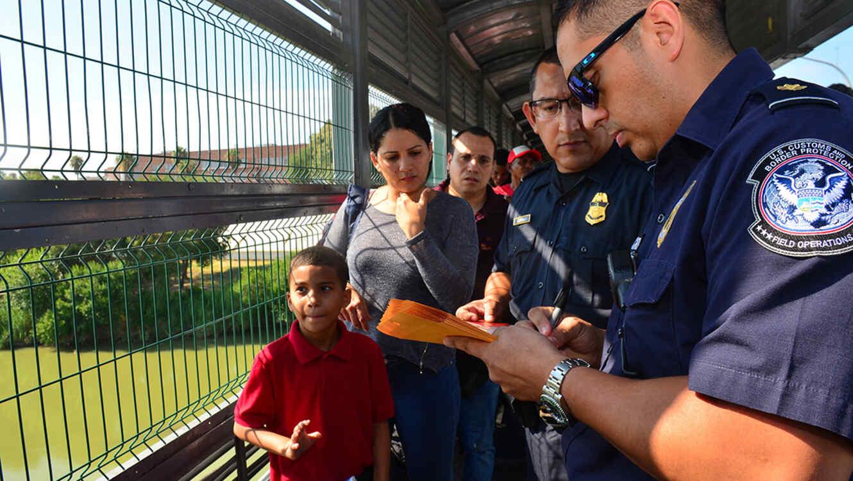 Un agente revisa los documentos de varios migranets que llegaron a la frontera estadounidense en Nuevo Laredo para solicitar asilo.