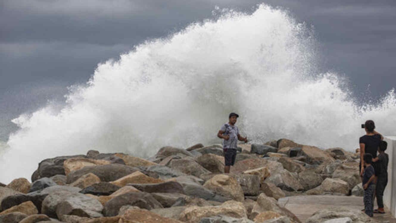 Un turista se posiciona este viernes para que le tomen una foto en Los Cabos, México, con a su espalda el fuerte oleaje provocado por el acercamiento del huracán Lorena.