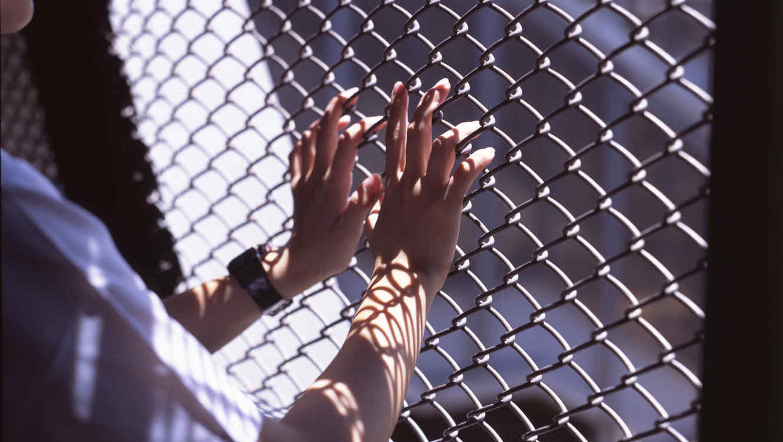 Una mujer toca con sus manos una cerca en una cárcel.