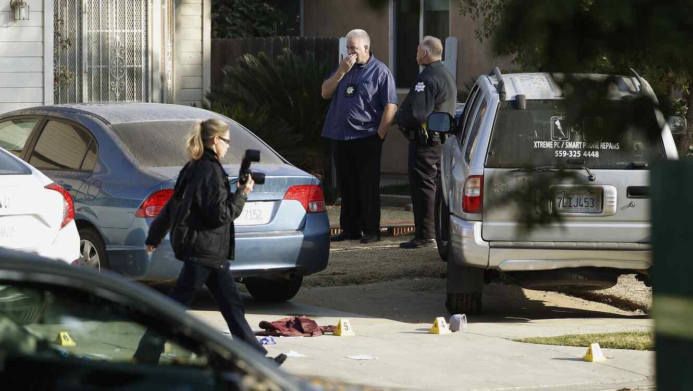 El investigador de la policía de Fresno, Brooke Passmore, a la izquierda, trabaja en la entrada de la avenida Lamona, donde se produjo un tiroteo en una fiesta en la casa que involucró múltiples muertes y lesiones en Fresno, California, el lunes 18 de nov