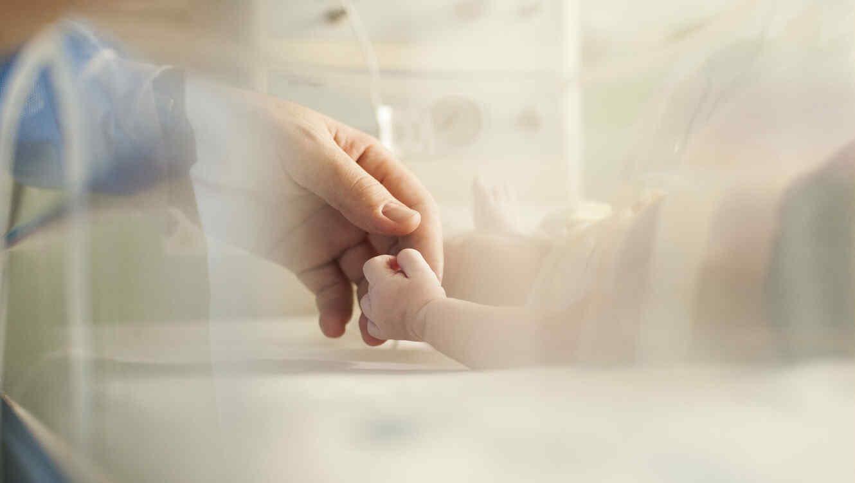 Papá sosteniendo la mano de su bebé