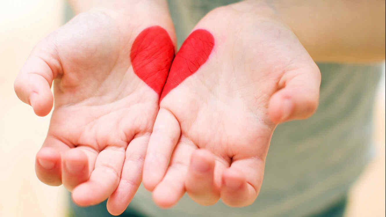 Manos con un corazón pintado