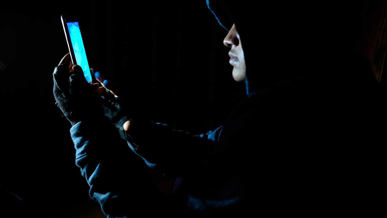Hooded hacker stealing perdonal data or bank information using smart phone