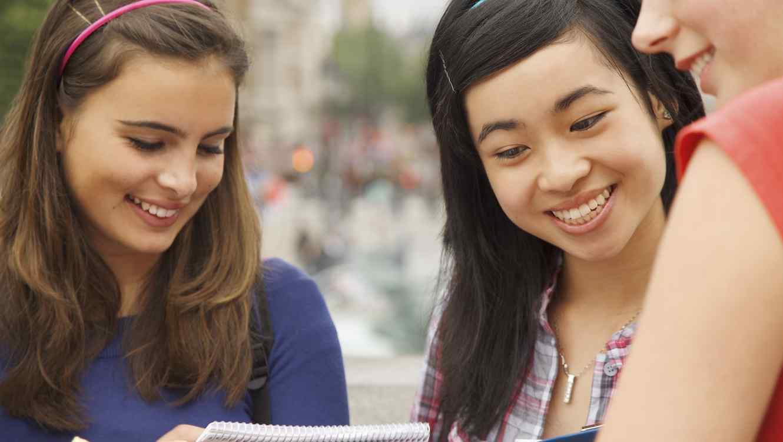 Chicas sonrientes mirando cuaderno