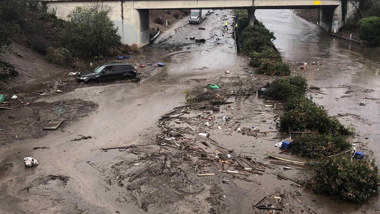 Carros varados y abandonados en una carretera inundada en Montecito, California