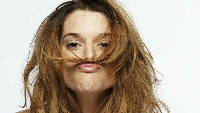 Mujer con el cabello sobre su boca