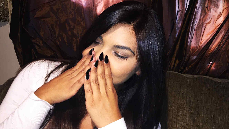 mujer con cabello oscuro con uñas negras puntiagudas