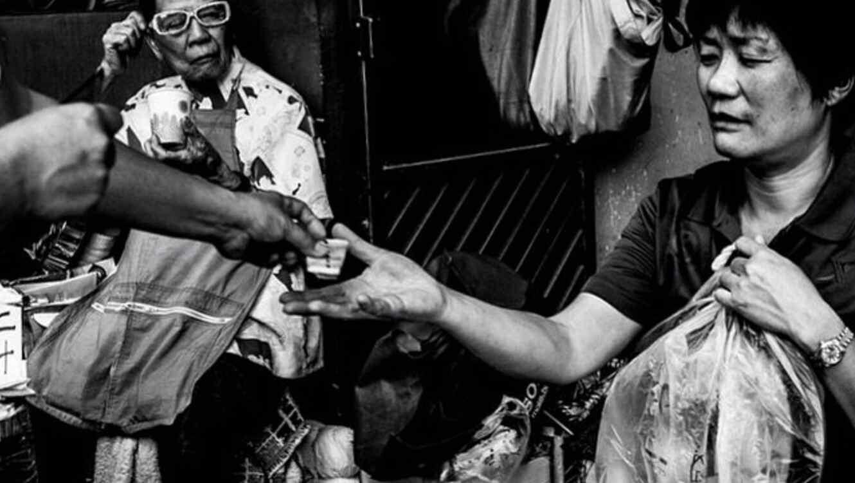 Mujer sosteniendo una bolsa y extendiendo la mano para recibir dinero