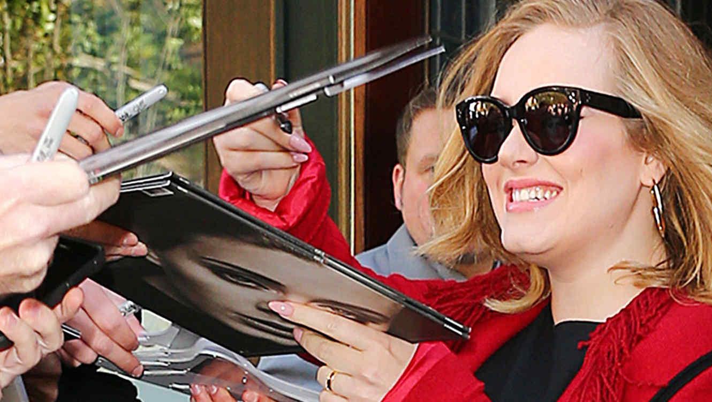Adele firmando autógrafos con abrigo rojo y gafas oscuras