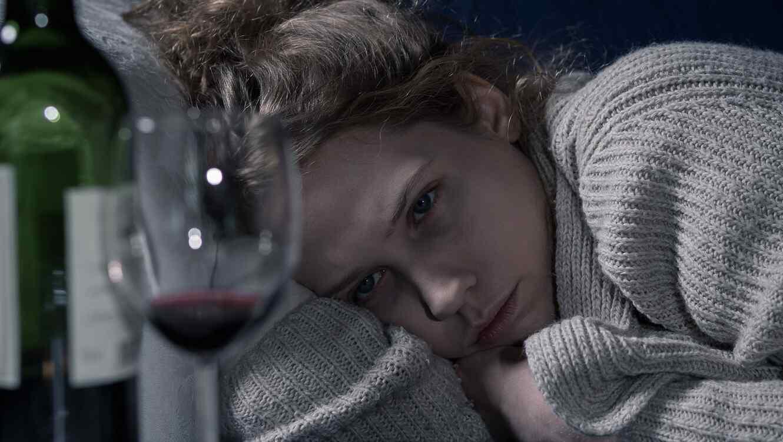Mujer recostada viendo una copa de vino