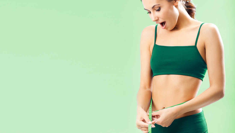 Mujer midiendo su cintura sobre fondo verde