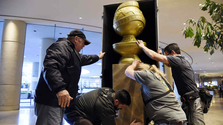Trabajadores colocan una estatua de los Globos de Oro en un día de preparativos