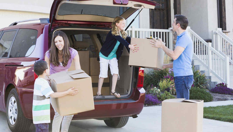 Familia bajando cajas del coche frente a la casa