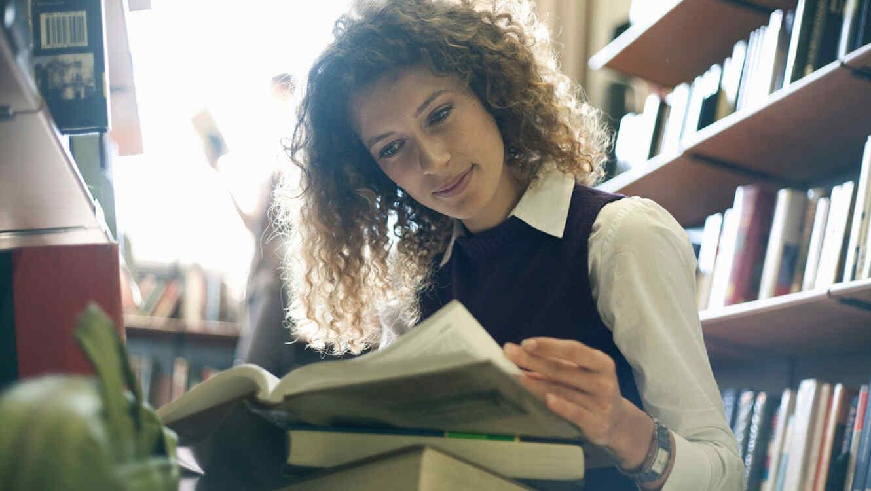 Mujer joven leyendo libros en la biblioteca