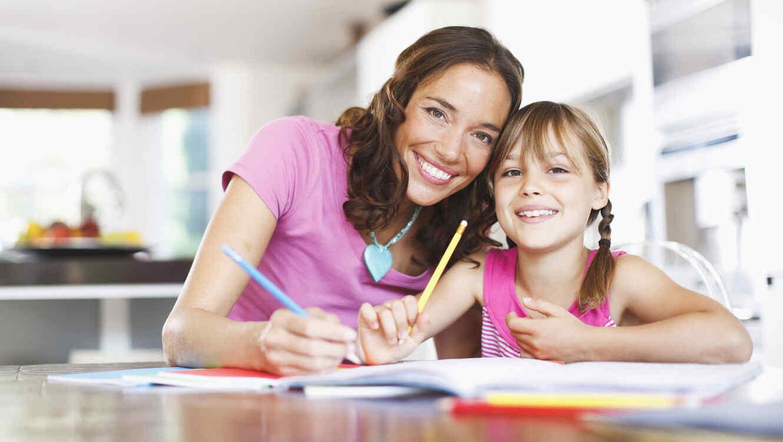 Madre ayudando a su hija de primaria con las tareas