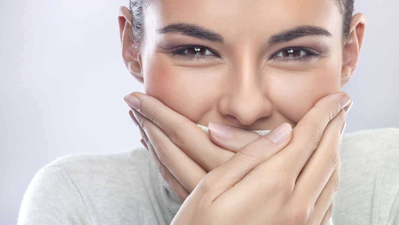 Mujer joven cubriéndose la boca con las manos