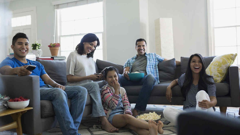 Familia hispana mirando televisión y comiendo palomitas