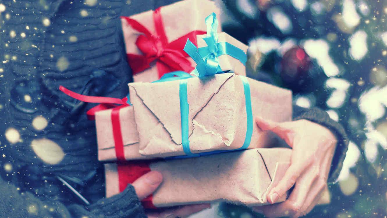 sosteniendo paquetes de regalos navideos