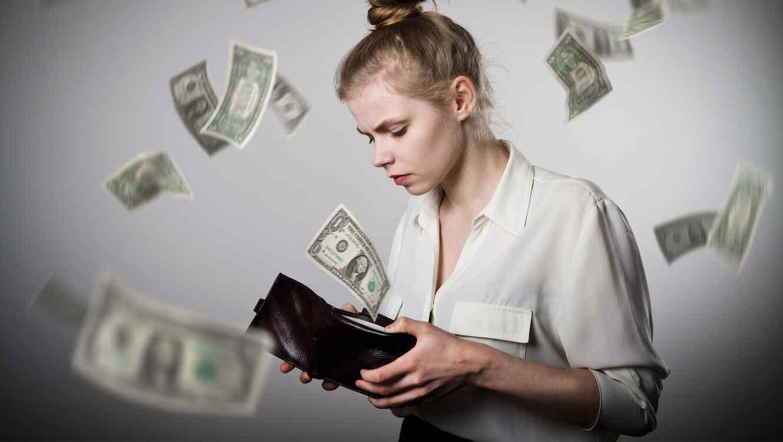 Mujer mira su cartera con preocupación