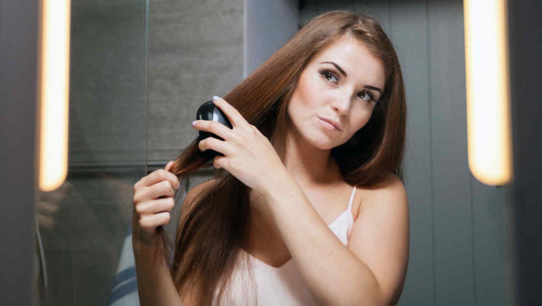 Mujer cepillándose el cabello frente al espejo.
