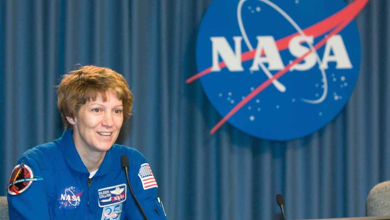Eileen Collins con cartel de NASA de fondo