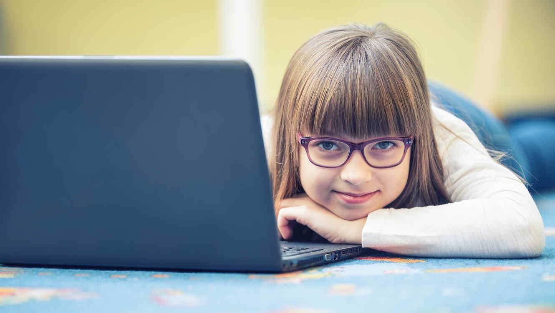Niña preadolescente recostada con una laptop